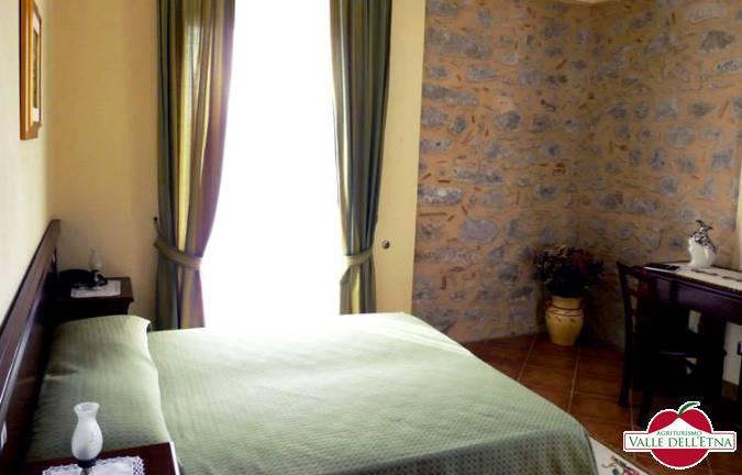 Camera doppia. Le camere doppia uso singola dell'Agriturismo Valle dell'Etna sono ampie, luminose e fornite di letto matrimoniale. Tutte le camere sono arredate in stile rustico e dotate di riscaldamento